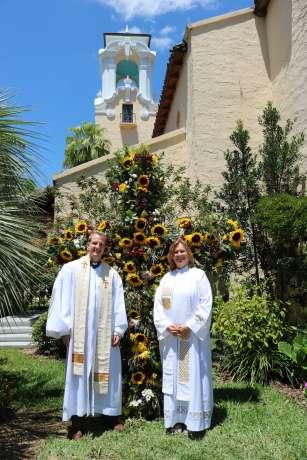 Pastors Aaron and Megan standing in front of the flowery Easter cross