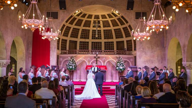 Wedding couple, wedding party, and guests listen to Pastor Megan in our historic sanctuary during the ceremony (Photo by Photo and Video by Liam)