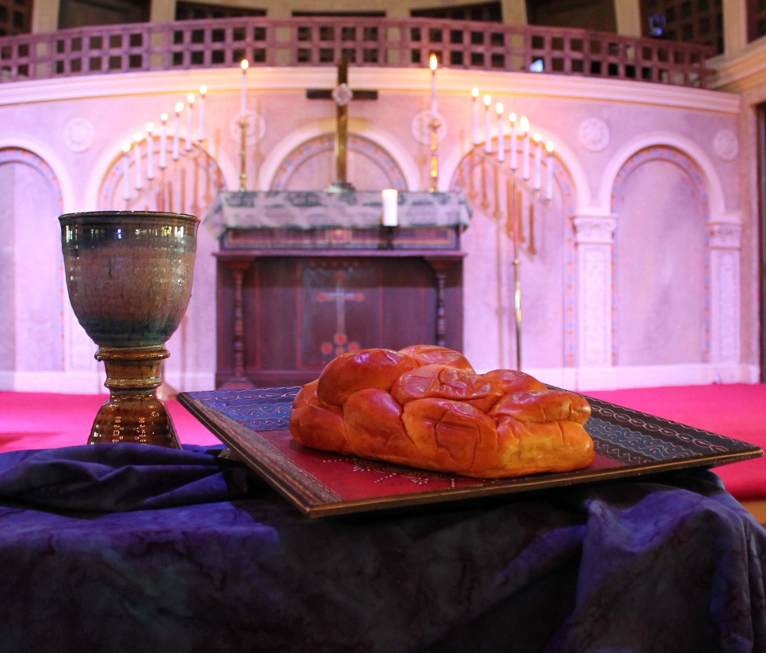 Chalice and loaf of bread in front of altar